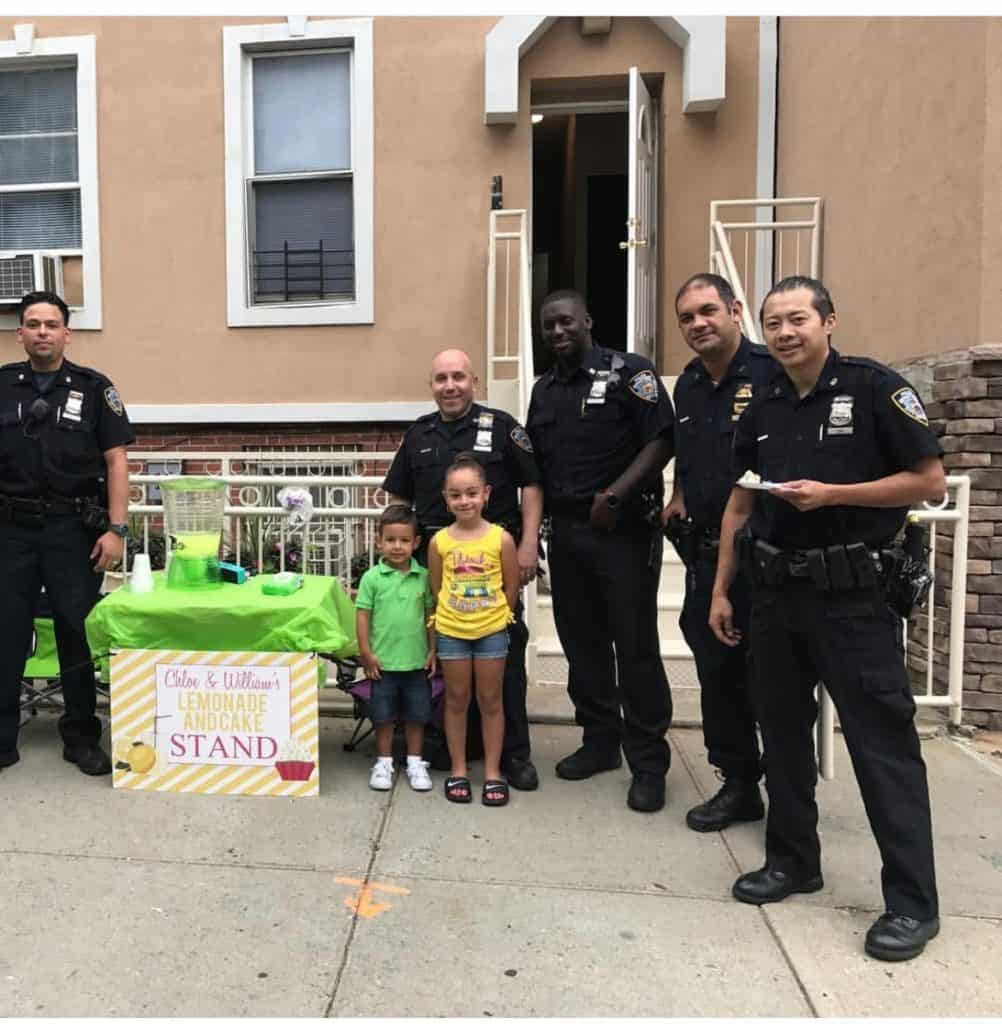 """William and Chloe with their """"police friends"""" from the 83rd Precinct at their first annual Lemonade and Cake Stand"""